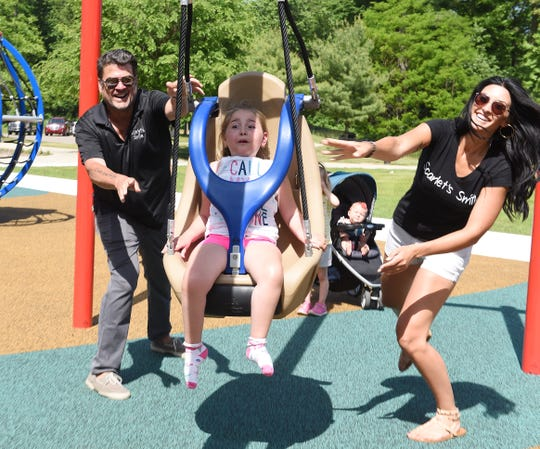 Scarlet Clark,7, gets a push on the zip line from  l-r, her grandfather Stephen Clark and mom Hillary Clark.