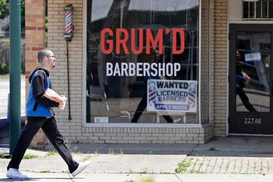 A man walks past Grum'D Barbershop, Friday, June 5, 2020, in Euclid, Ohio. U.S. unemployment dropped unexpectedly in May to 13.3% as reopened businesses began recalling millions of workers faster than economists had predicted, triggering a rally Friday on Wall Street.