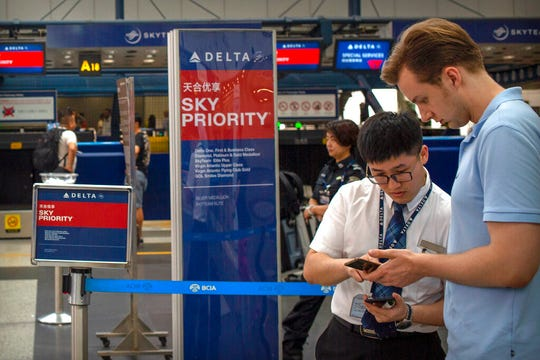 In this July 6, 2018 photo, a staff member talks with a traveler at the Delta Air Lines check-in counters at Beijing Capital International Airport. The Trump administration said Friday it will let Chinese airlines operate a limited number of flights to the U.S.