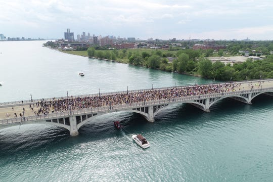 A drone image of protesters marching across the MacArthur bridge which connects mainland Detroit to Belle Isle.