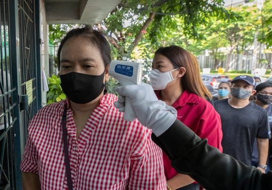 An officer checks the temperature ofWannapa Kotabin, a 38-year-old kitchen assistant at an Italian restaurant, in front of Social Security office for claim unemployment benefit in Bangkok, Thailand.
