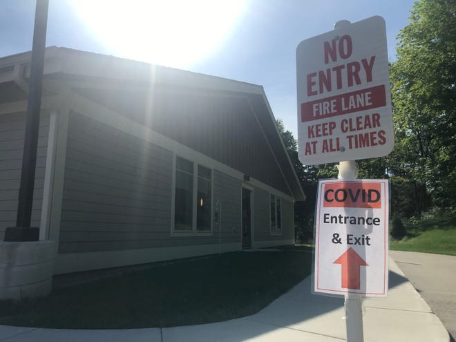 """A sign at the Ingham County Medical Care Facility points to the """"COVID entrance & exit"""" on Friday, June 5, 2020."""