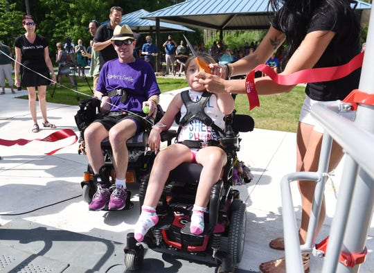 Scarlet Clark, 7, cuts the ribbon to open the park with the help of her mom Hillary.