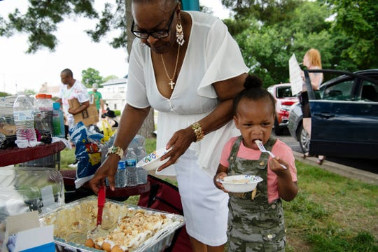 Charlisse Irvine, 2, samples the banana pudding with Janice King during a break in protesting against police violence in African-American communities in the United States on the riverfront in Evansville Thursday afternoon, June 4, 2020.