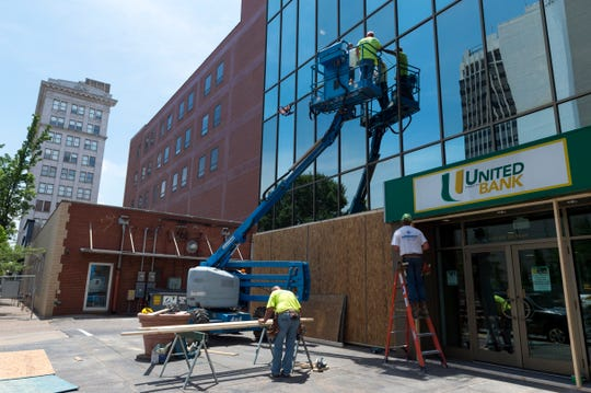 Workers with Midwest Contracting install floodlights and board up windows at United Fidelity Bank in Downtown Evansville, Ind., Friday afternoon, June 5, 2020. The bank is one business that has taken steps to prepare for potential damage due to rumors circulating around Saturday's protest.