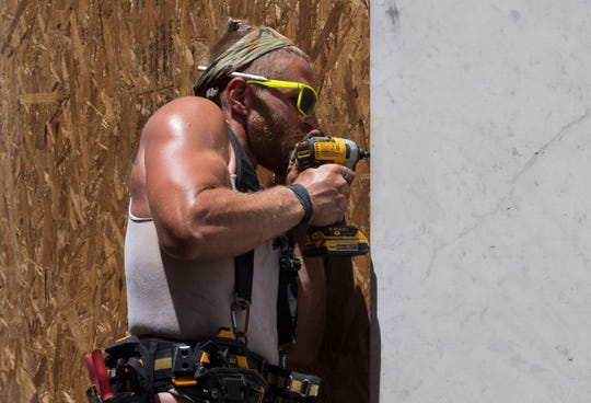 Sam Hayman with Midwest Contracting boards up windows at United Fidelity Bank in Downtown Evansville, Ind., Friday afternoon, June 5, 2020. The bank is one business that has taken steps to prepare for potential damage due to rumors circulating around Saturday's protest.
