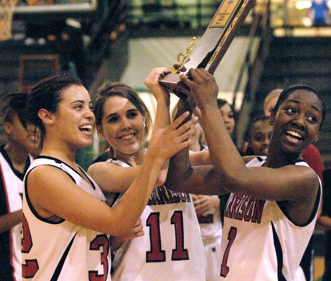 Harrison's Genesis Robinson (left), Kayla Woodruff and Khristian Hart hold up the trophy after winning the local Class 4A sectional title in 2010 at North.