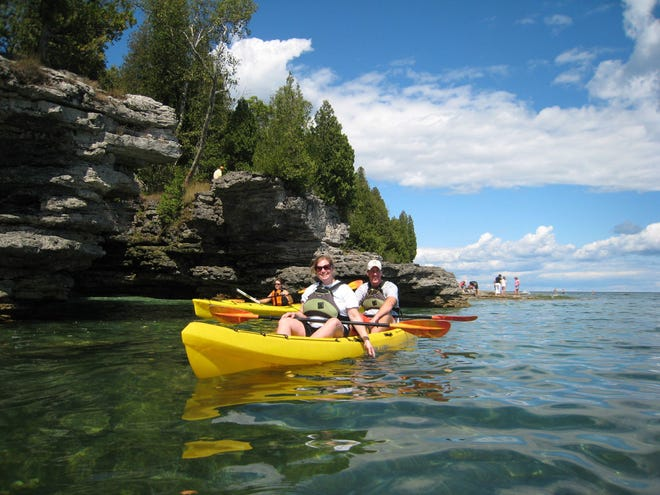A Door County Kayak Tours group paddles along the Door County shoreline. For more about tours, visit doorcountykayaktours.com.