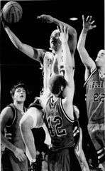 """Allen """"A.J."""" Longsoldier (in white) goes in for a layup against Froid-Medicine Lake during the 2007 Class C State Basketball Tournament at Four Seasons Arena. Defending for the Red Hawks are Colton Justice (left), Dan Hancock (42) and Kyle Guenther (22)."""