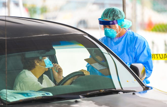 In this file photo from June, Public Health employees offer free COVID-19 tests to residents taking advantage of drive-through testing.