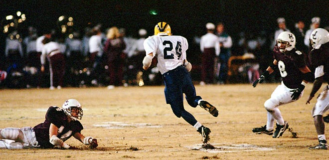 Central Hardin halfback Gene Blair runs through an open hole in the Henderson County secondary during the 1997 first-round playoff game at Colonel Stadium. Josh Abner lays at left, while John Siewert and Jeff Davis come in to make the tackle from the right.