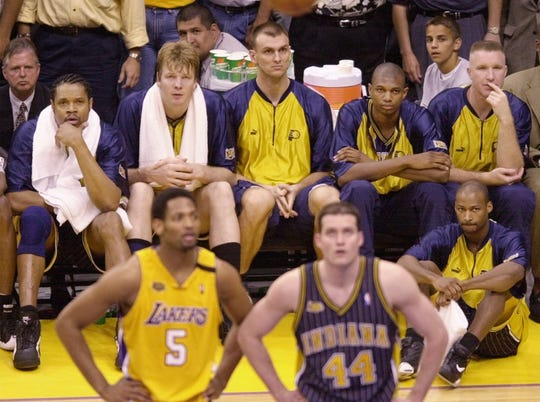Members of the Indiana Pacers, from left, Sam Perkins, Rik Smits, Zan Tabak, Jonathan Bender, Chris Mullen and Travis Best (on floor) watch as teammate Austin Croshere (44) and Los Angeles Lakers' Robert Horry play in the final moments of Game 6 of the NBA Finals in Los Angeles, June 19, 2000. The Lakers won the game 116-111.