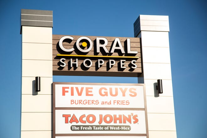 """A sign at the """"Coral Shoppes"""" for Five Guys Burger and Fries as well as Taco John's are seen, Tuesday, June 2, 2020, in Coralville, Iowa. The Five Guys location opened in March."""