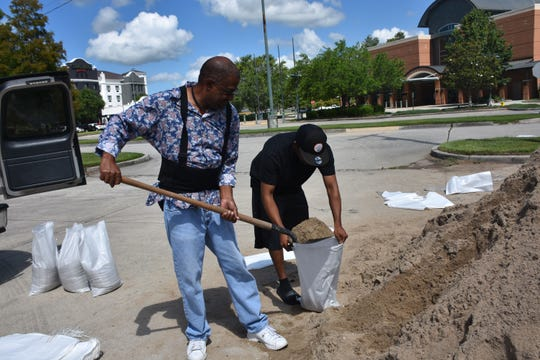 Ed Lewis and Nick Williams fill sandbags in preparation for Tropical Storm Cristobal in the parking lot near the Houma-Terrebonne Civic Center.