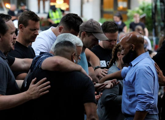 Evan Saunders, right, leads a prayer for first responders at the peace rally in Zane Square Thursday, June 4. The event was dedicated to citizen unity and speaking out against police brutality towards people of color after George Floyd's death in police custody in Minneapolis May 25.