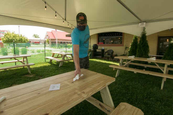 Wooden Spoon restaurant General Manager Jordan Mack sets one of the picnic tables added to a tented dining area in front of the Brighton eatery Friday, June 5, 2020.