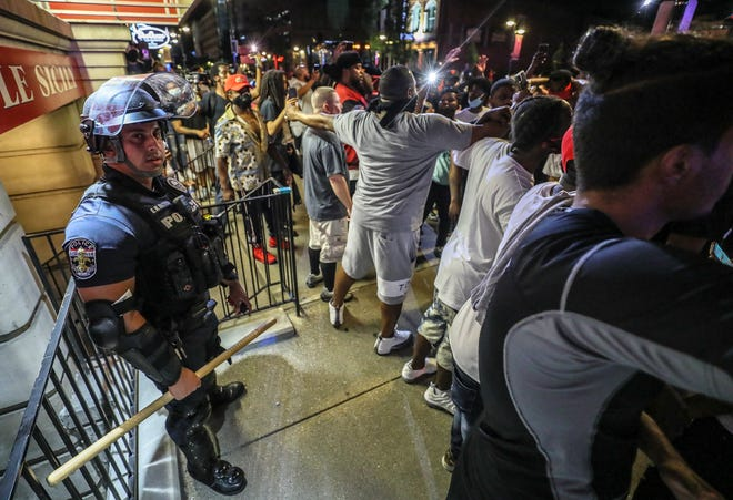 Protesters surround Louisville Metro Police Department officer Galen Hinshaw in front of Bearno's restaurant on Thursday, May 28, 2020 in Louisville, Kentucky.  Five strangers, including Julian De La Cruz, Ricky McClellan and Darrin Lee Jr., linked arms to keep the crowd from getting to Hinshaw.