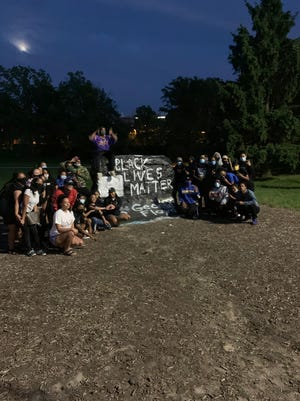 Peaceful protestors pose next to the Rock on Michigan State's campus as part of a candlelit vigil held in honor of George Floyd, who was killed by a Minneapolis police officer.
