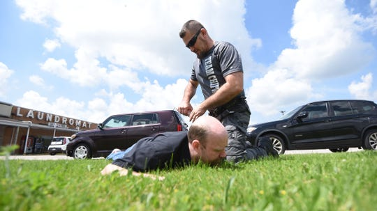 Shawn Chitwood demonstrates on Aaron Behr a method to detain a suspect without placing a knee on the neck.