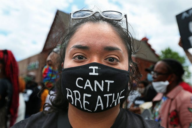 Alondra Garcia, a second grade MPS teacher wears a mask she made to remember George Floyd who was killed this week by a Minneapolis police officer during a protest at 26th and Center streets on Friday, May 29, 2020.  Garcia said she had friends who have experienced police brutality and she wanted her students to know that she was standing with her brothers and sisters and that justice needs to be served. A crowd of more than 500 gathered for the protest at 26th and Center streets. A smaller crowd of about 300 marched from the  rally to downtown Milwaukee continue to let their voices be heard police brutality on a local and national level.