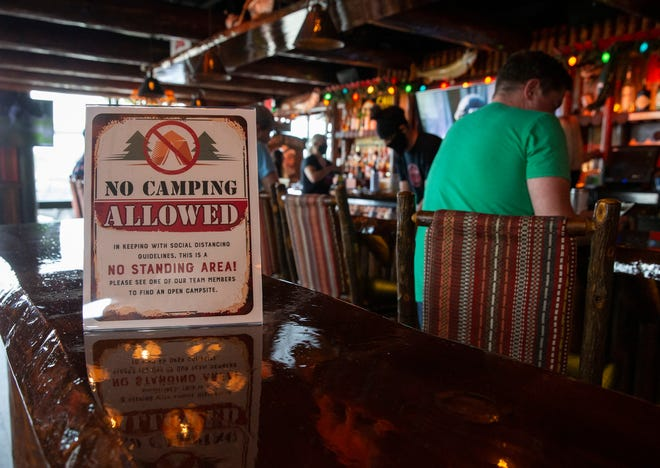 A sign is put on a table in Camp Bar Third Ward to remind customers keep distancing on Friday, June 5, 2020, in the Historic  Third Ward. Bars and restaurants in the city of Milwaukee were allowed to reopen at 25% capacity for in-person service.