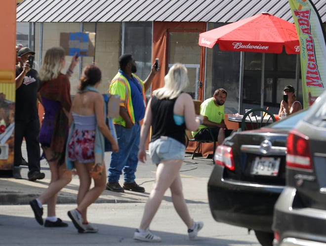 Fiesta Cafe on South First Street is shown in June, with patrons dining as unrelated protests took place outside.