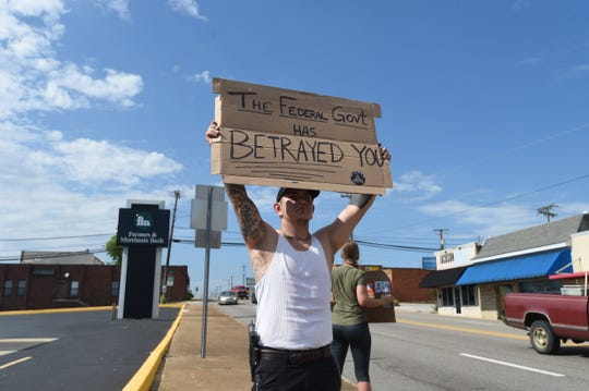 Eli Freeman holds up a protest sign near the courthouse square in Mountain Home late Friday afternoon.