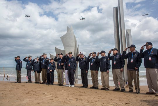 FILE - In this Monday, June, 3, 2019, file photo, World War II veterans from the United States salute as they pose in front of Les Braves monument at Omaha Beach in Saint-Laurent-sur-Mer, Normandy, France. In sharp contrast to the 75th anniversary of D-Day, this year's 76th will be one of the loneliest remembrances ever, as the coronavirus pandemic is keeping nearly everyone from traveling. (AP Photo/Rafael Yaghobzadeh, File)