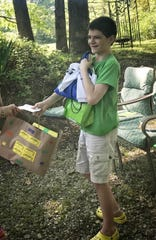 Aiden Ellis smiles as he receives gifts during a parade past his St. Louisville home, celebrating his transition from I Am Boundless to Licking Valley.