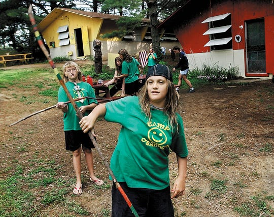 Children, twirl their walking sticks while playing around at Camp O'Bannon in this file photo.