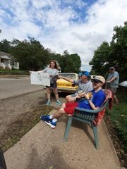 Michael Lehman (foreground) smiles as a parade moves past his Newark home, celebrating his graduation from I Am Boundless and Newark High School.