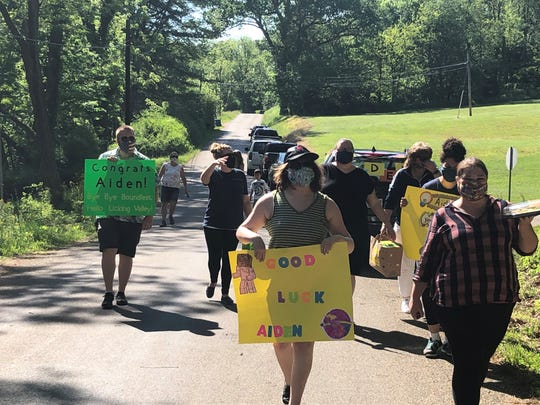 People march past the St. Louisville home of Aiden Ellis, during a parade celebrating his transition from I Am Boundless to Licking Valley.