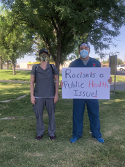 Jesus Gonzalez and Stefanie Bennett, students of Burrell College of Osteopathic Medicine, hold signs in protest of George Floyd's death in Minneapolis in late May.