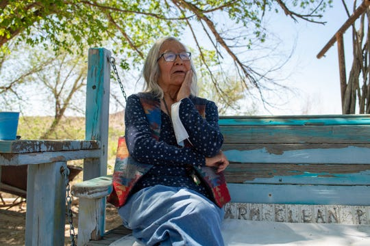 "Gloria Emerson sits beside the San Juan River near her home in Shiprock. The words behind her remind visitors to ""keep farm clean please."""