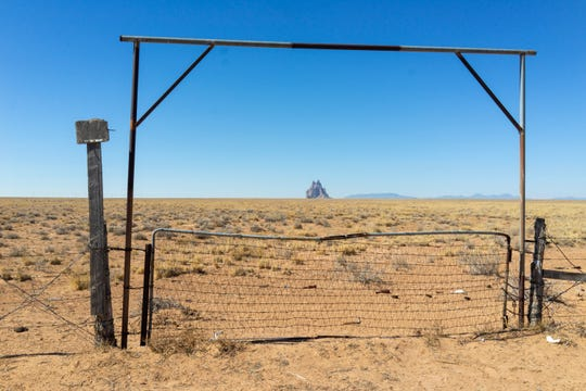 The iconic Shiprock formation is pictured framed by gate on the Navajo Nation.