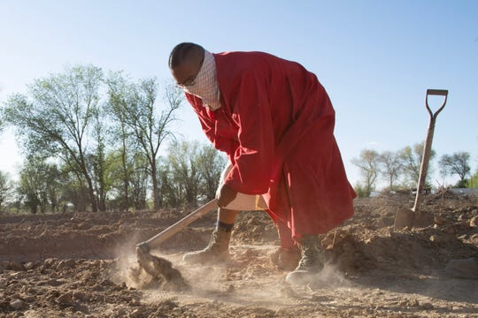 Zefren Anderson breaks ground to plant potatoes on a farm in Shiprock.