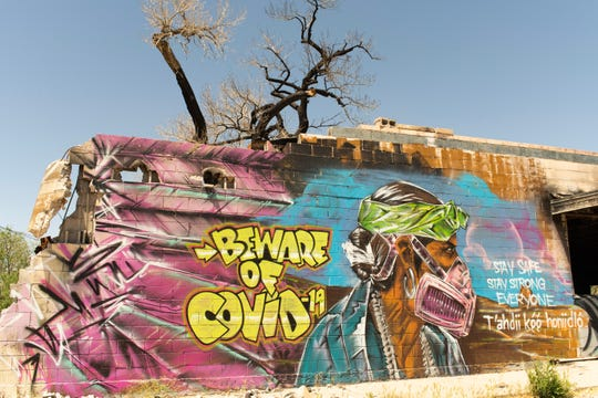 A mural in Shiprock, depicting a man in traditional dress with a respirator, warns residents about COVID-19.