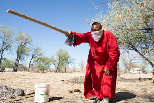 Zefren Anderson points with his hoe on a farm where he's planting food in Shiprock.