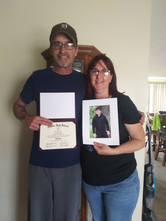 Larry and Christy Wagner hold a picture of their late son, Joe and his high school diploma on June 3, 2020.
