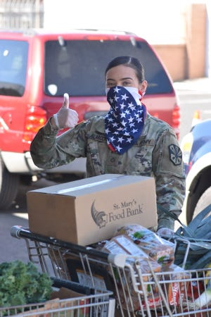 A National Guard volunteer helps St. Mary's Food Bank distribute food to individuals and families during the COVID-19 crisis.