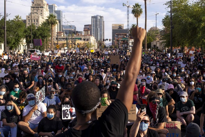 Protesters watch as Lee Percy Christian holds up his fist during a march against police brutality on June 4, 2020, in downtown Phoenix.