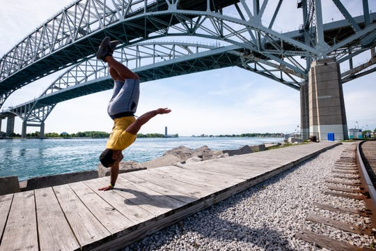 Local tricker Dom Lewis does a one-handed back handspring on the boardwalk near the Blue Water Bridge Thursday, June 4, 2020, in Port Huron.