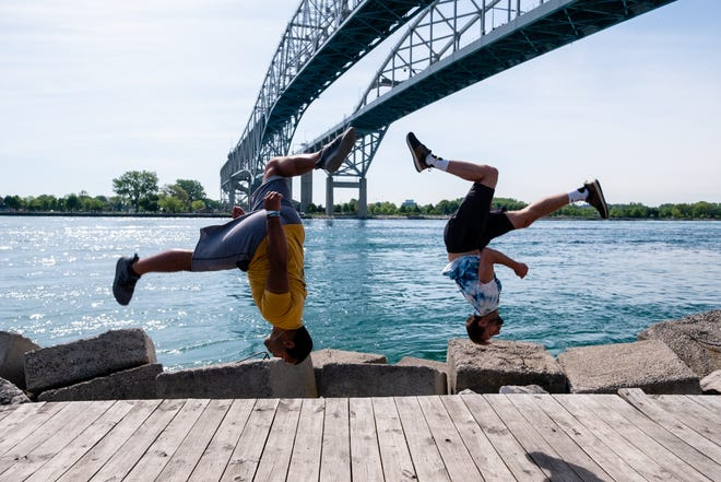 Dom Lewis, left, and Brandon Schwerin, both members of the local tricking team Every Day Heroes, do synchronized flash kicks Thursday, June 4, 2020, on the boardwalk near the Blue Water Bridge in Port Huron.