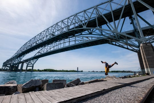 Local tricker Dom Lewis does a flash kick on the boardwalk near the Blue Water Bridge Thursday, June 4, 2020.