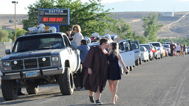 Matthew Hawley and Alyssa Medeiros kiss as they walk past a row of cars Thursday night.