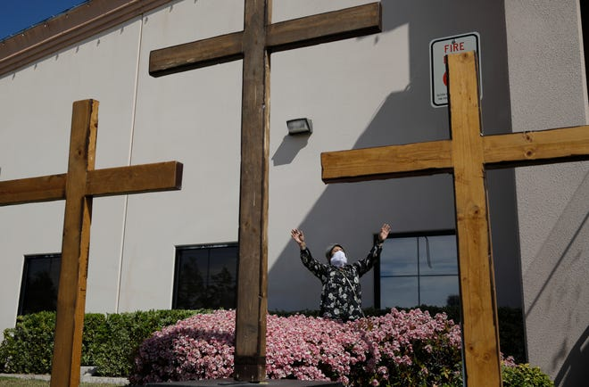 Norma Urrabazo prays while wearing a face mask before speaking at an Easter drive-in service at the International Church of Las Vegas, in Las Vegas. Nevada's lawyers are stepping up their defense of Gov. Steve Sisolak's 50-person cap on religious gatherings in a legal battle with leaders of Calvary Chapel Dayton Valley, a rural church who say it violates their constitutional right to exercise their beliefs.