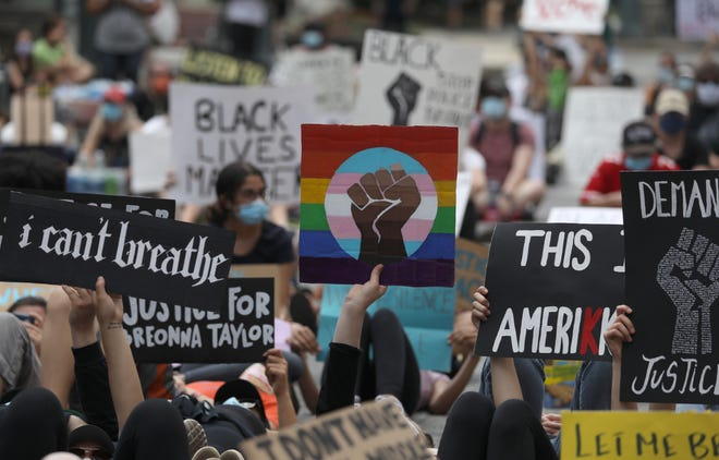 Signs are held up as hundreds of protesters silently lie in the street for eight minutes during the Black Lives Still Matter protest in downtown Rochester Friday, June 5, 2020. The eight minutes marked the amount of time that George Floyd, a black Minnesota man, lay before dying with a police officer's knee on his neck.