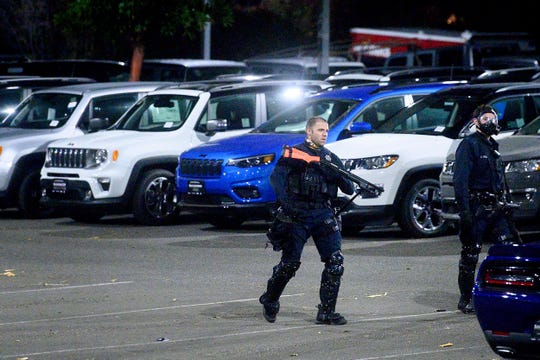 FILE - In this Monday, June 1, 2020, file photo, a police officer searches a San Leandro, Calif., car dealership shortly after multiple vehicles were stolen. Police say many of the smash-and-grab thefts have been carried out by caravans of well-coordinated criminals that have coincided with or followed protests over the death of George Floyd, who was killed by a Minneapolis police officer who pressed his knee into Floyd's neck. Nearly 75 vehicles were stolen Sunday, including models driven through glass showroom doors to escape. (AP Photo/Noah Berger, File)