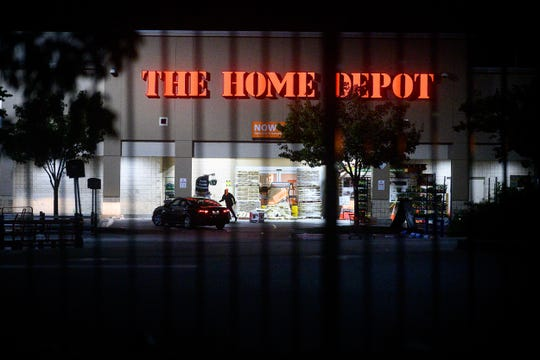 FILE - In this June 1, 2020, file photo, a man leaves a vandalized Home Depot store in Oakland, Calif. Police say many of the smash-and-grab thefts have been carried out by caravans of well-coordinated criminals that have coincided with or followed protests over the death of George Floyd, who was killed by a Minneapolis police officer who pressed his knee into Floyd's neck. (AP Photo/Noah Berger, File)