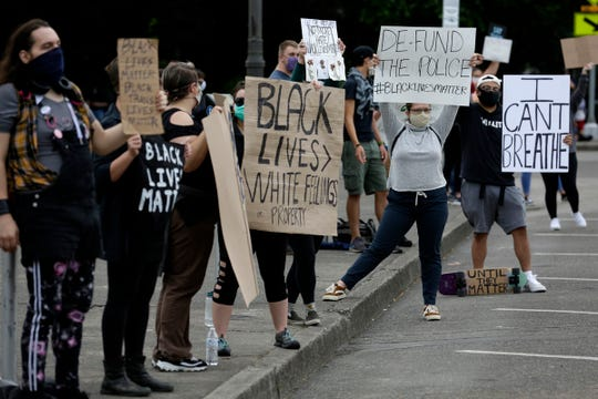 Demonstrators hold signs toward passing cars during a protest of the death of George Floyd in front of the Oregon State Capitol Building in Salem, Oregon, on Thursday, June 4, 2020.